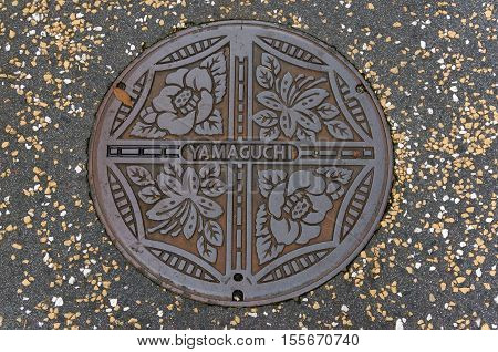 Yamaguchi Japan - September 5 2016: Manhole cover design in Yamaguchi. Japanese manhole covers come in a variety of designs depending on locality utility type and the manufacturer of the cover