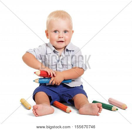 Cheerful little boy in a shirt and shorts, sits and holding a large pencils isolated on white background.