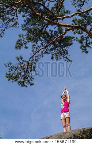 a Young woman standing on cliff with outstretched arms and enjoying valley view