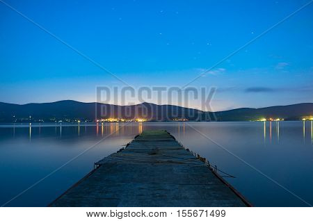 Old jetty on lake Yamanaka with distant city lights on the horizon. Night landscape photo. It is popular tourist destination for Mount Fuji climb. Yamanashi prefecture Japan