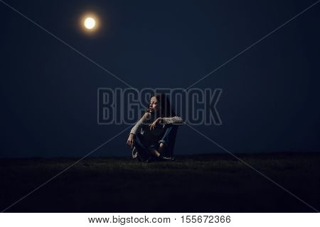 Pretty girl beautiful young woman sits on mountain top at night on moon light