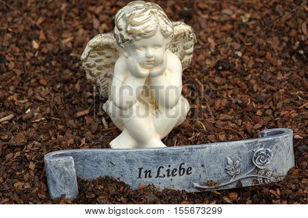 a little angel sculpture decorate in small garden with a sign in front it - in love - in German