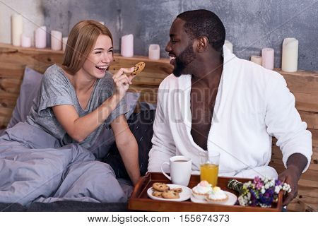 Pleasure and leisure. Young delighted international couple having breakfast and feeding each other with cookies while laughing in bed.