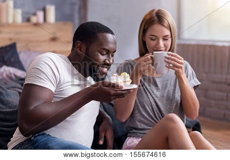Moment of happiness. Overjoyed young international couple drinking tea and eating cupcakes while lying in bedroom.