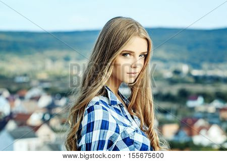 Pretty girl young beautiful woman with blue eyes and long curly blond hair in shirt poses outdoors on natural background