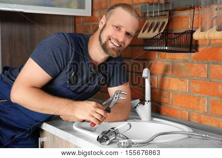 Handsome plumber replacing faucet in kitchen, close up view