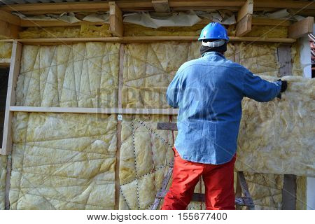 Builder wearing blue protective safety hat insulating wooden house with mineral wool