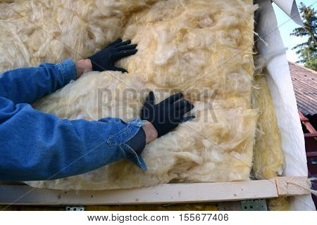 Builder hands wearing glove insulating wooden house with mineral wool