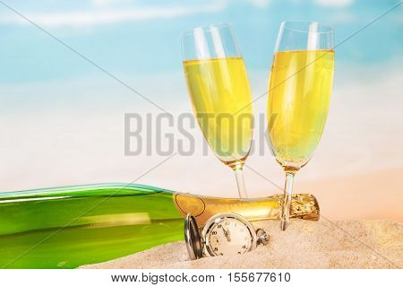 Bottle and two glasses with champagne, clock in the sand against the sea.