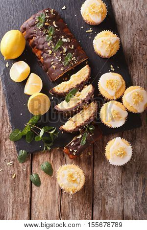 Sliced Lemon Cake With Chocolate And Lemon Muffins With Icing And Zest Close-up. Vertical Top View