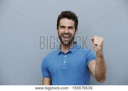 Ecstatic man cheering at camera studio shot