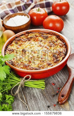 Fish casserole with tomatoes and herbs on the table