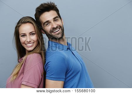 Back to back couple in polo shirts portrait