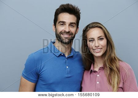 Happy Couple in polo shirts smiling for camera
