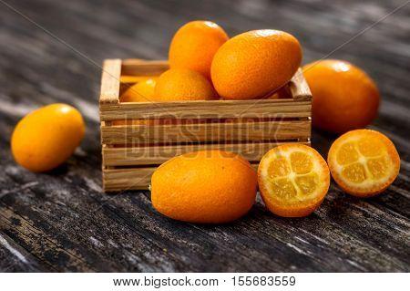 Raw Organic Kumquats on wooden background .