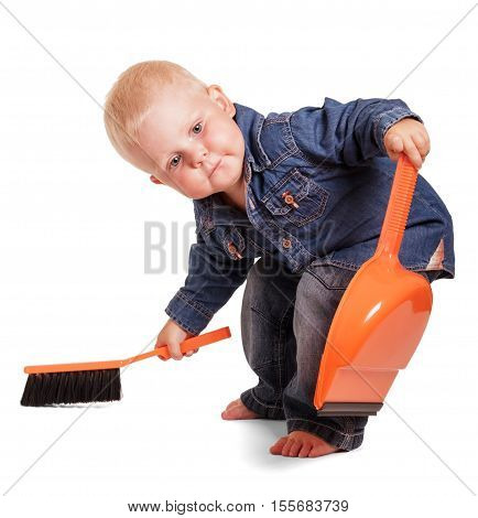 Cute little boy in a blue shirt and jeans, holding a dustpan having bent and sweeping brush isolated on white background.