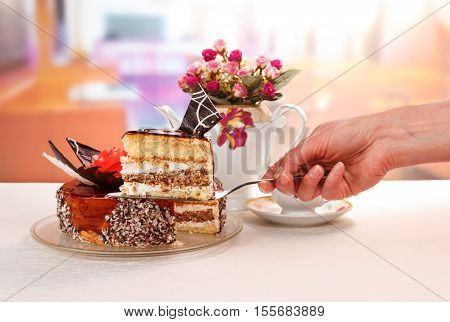 Hand holds a scapula with a piece of chocolate cream cake and cup of tea on a background of the kitchen.