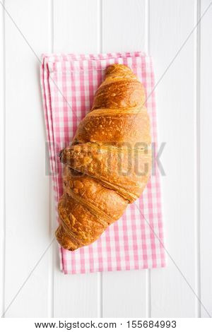 Tasty buttery croissant on checkered napkin. Top view.