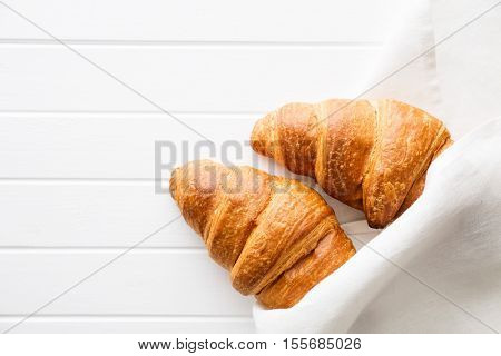 Tasty buttery croissants in napkin. Top view.