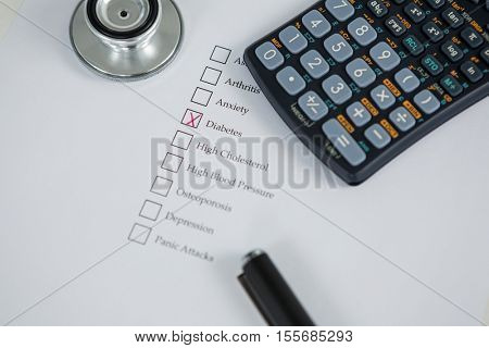 Close-up of health evaluation form with diabetes check and calculator, stethoscope on table