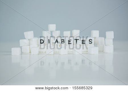 Sugar cubes spelling out diabetes on white background