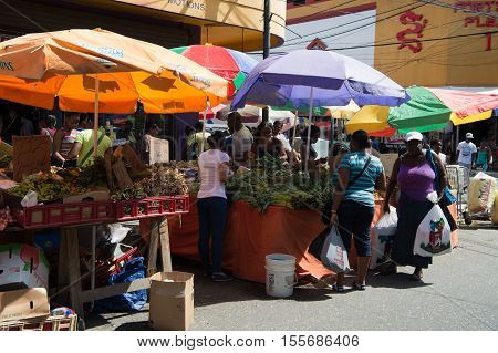 Port of spain Trinidad and Tobago - November 28 2015: busy local south market of vegetables and fruit with people outdoors on sunny summer day on streetscape background
