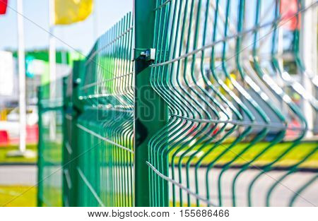Fence of green iron bars in sunny summer day