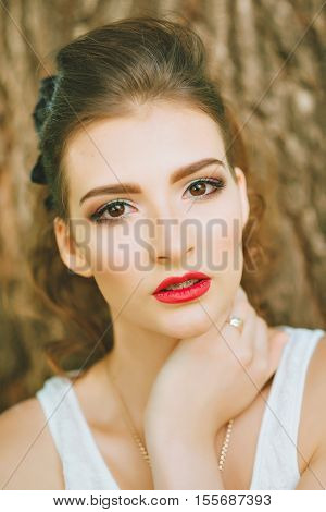 Woman with red lipstick and colored makeup, portrait in nature. Looking at the camera