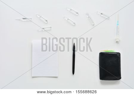 Medical composition with syringe, ampules, purse and notebook on white background. Top view of doctor workplace. Flat lay mock up.