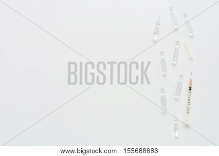 Medical composition with syringe and ampules on white background. Top view of doctor workplace. Vertical flat lay mock up.