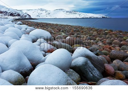 Beach with big round stones on the coast of the Barents Sea Arctic