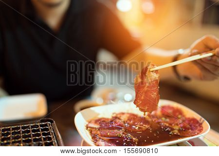 Raw beef or pork slice for charcoal grill Yakiniku Japanese style barbecue man using chopsticks street food concept depth of field and soft light effect