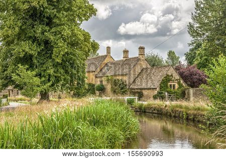 River Eye and reeds with historic stone cottages at Lower Slaughter, in the English Cotswolds, said to be one of the prettiest villages in England.