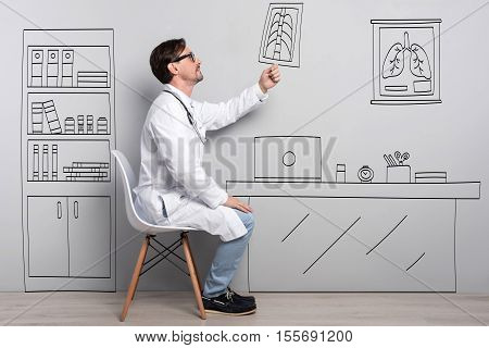 Lovely job. Positive handsome young man smiling and holding roentgenogram while sitting on the chair.