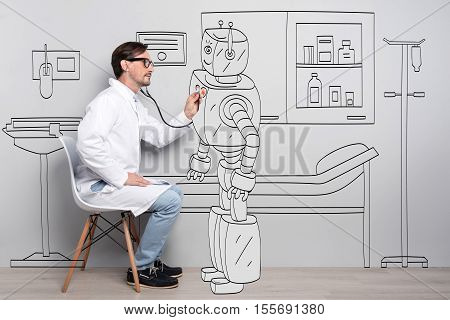 Everyone have a heart. Young talented man using stethoscope and examining robots heart while sitting on the chair
