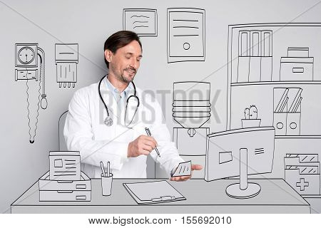 I love medicine. Delighted handsome man smiling and making prescription while sitting by the table.