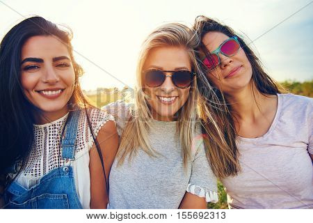 Three beautiful young women in sunglasses standing close together outdoors for concept about friends