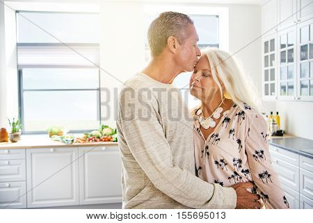 Handsome man kissing wife with closed eyes and calm expression on forehead in kitchen. Includes copy space.