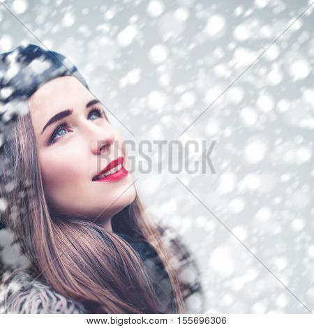Beautiful Model Woman Looking Up on Snowfall Winter Background. First Snow
