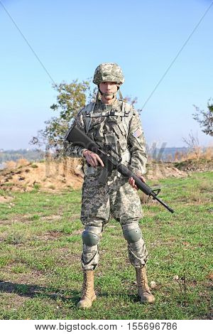 Soldier with rifle standing at military firing range near river