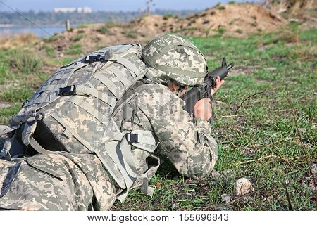 Soldier in camouflage taking aim at military firing range, close up