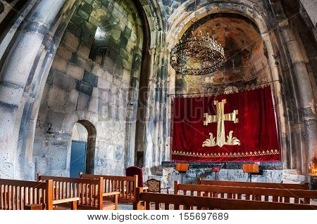 HAGHPAT ARMENIA - MARCH 25 2016: Inside a Haghpat Monastery - famous landmark in Armenia. Rows with wooden seats in front of an altar. Chandelier and beautiful religious decoration