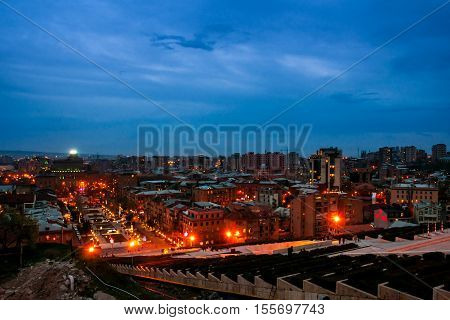 Night in Yerevan Armenia from Cascade Ararat mountain at the background. Nightlife with people and car traffic in the capital of Armenia. Sunset in Yerevan