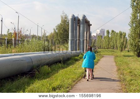 The pipes pass through the grass and bushes. The old tubes and lay for a long time. All overgrown with plants. In the background the red of a multistory building. The road is a woman with a baby pram (baby carriage).