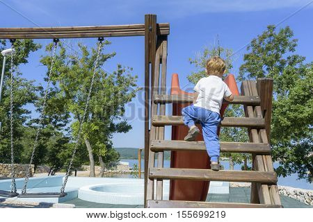 Little Boy Climbing Ladder On Slide