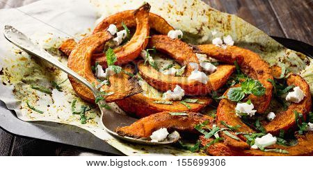 Roasted, baked pumpkin with addition aromatic herbs, goat cheese and mint. Healthy food concept with copy space.