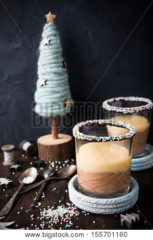 Chocolate dessert with Custard cream on old dark wooden background with decorative christmas tree.
