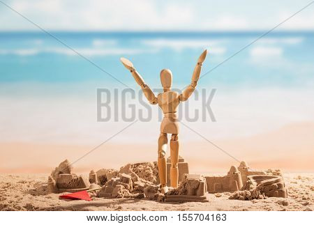 Battered sandcastles and a wooden doll with hands up against the background of the sea.