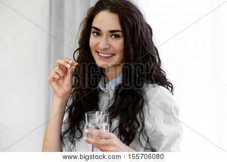 Portrait of young woman with fish oil capsule and glass of water, on light background