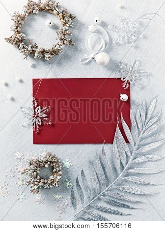 Still life with silver and white Christmas decorations and a blank red  card